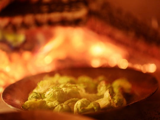 Brussels sprouts cook in the wood burning oven at Selden Standard in Detroit.