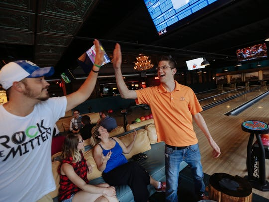 Mackenzie Urban of Windsor, Ontario, right, high-fives with Shane Madaus of Shelby Township after Urban threw a strike. They were bowling on Thursday at Punch Bowl Social in Detroit.