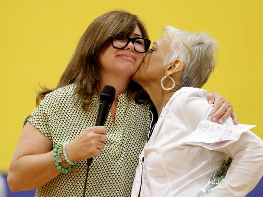 Jalenm Miller kisses her sister, Sharla Hartgraves, on the cheek during a surprise assembly for Jalen Miller, a library assistant, at Gervais High School in Gervais, Ore., on Friday, May 8, 2015. Miller was diagnosed with cancer in August 2014 and has always dreamed of visiting Disneyland with her grandchildren.