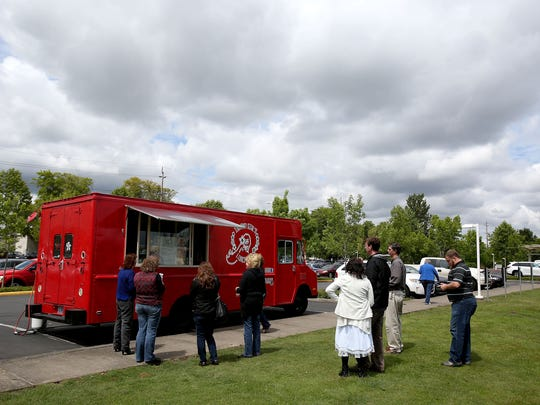 Customers wait at the Island Girl Lunchbox food cart at the Oregon Lottery Commission.