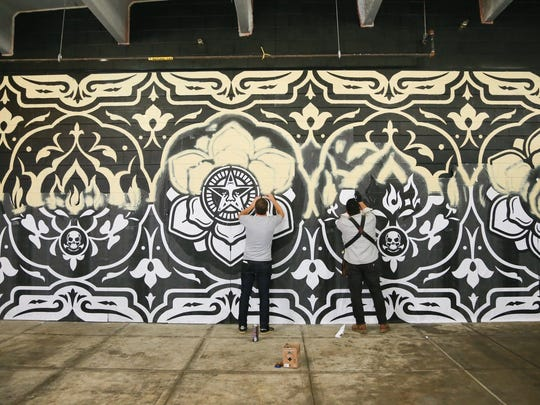 Artist Shepard Fairey and his team used razors, stencils, spray paint and adhesive as they created the mural in the Belt alley in the Z parking garage.