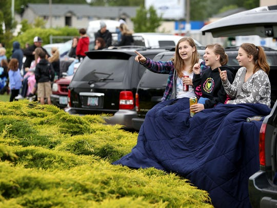 Harley Billings, left, 15, with her sisters Marina, 12, and Hanna, 11, watch Saturday's Iris Festival Parade from a parking lot along River Road N in Keizer.