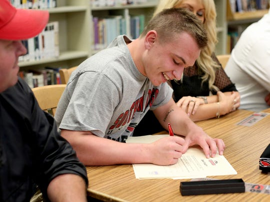 Jake Vaughn signs a letter of intent to wrestle at Southern Oregon. Vaughn is flanked by his parents, Jason and Jodie Vaughn, during a signing day ceremony Monday, May 18. .