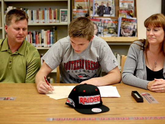 Logan Holmquist signs a letter of intent to wrestle at Southern Oregon, sitting between his parents, Dave Holmquist and Chrissy Borregard, during a signing day ceremony Monday, May 18, at Sprague High School.