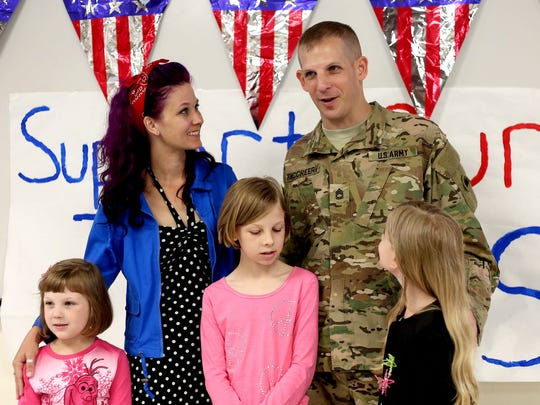 Army Sgt. 1st Class Matthew McCreery stands wit his wife, Rachel, and their daughters, Sierra, 10, Kinley, 8, and Ashlyn, 6, after a surprise homecoming during a Memorial Day assembly at Brush College Elementary School in West Salem on Thursday, May 21, 2015. McCreery just returned from a year-long deployment in Afghanistan.