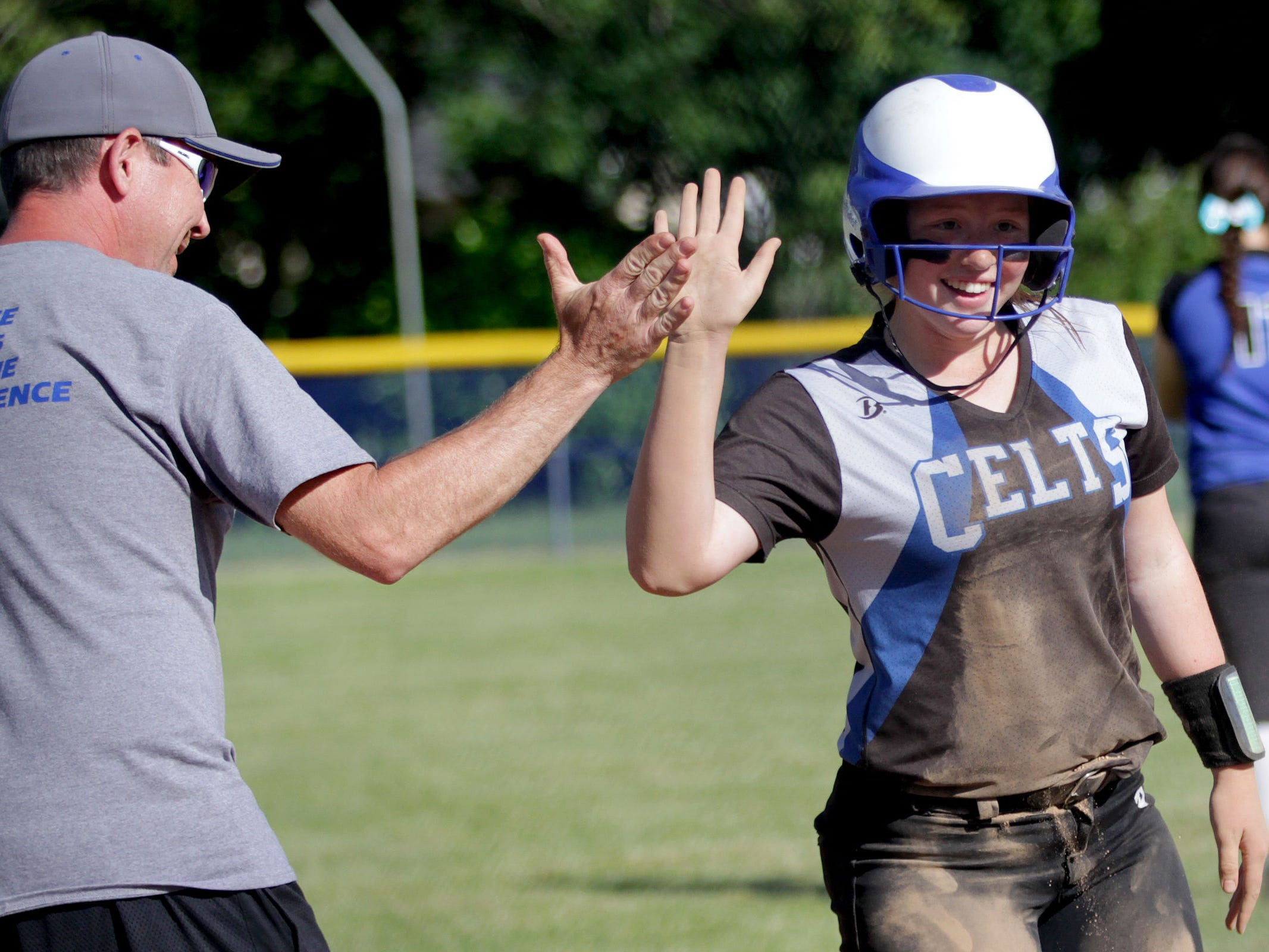 McNary's Hannah Carr (11) high-fives head coach Kevin Wise in the Gresham vs. McNary softball game, in the first round of the OSAA class 6A state playoffs, at McNary High School in Keizer on Monday, May 25, 2015. McNary won the game 11-7.