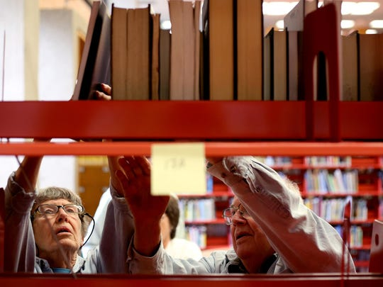 Volunteers Pat Ehrlich (left) and her husband Jim Willhite help the Willamette Valley Genealogical Society move books and other materials from the Oregon State Library to the Salem Public Library on Monday, June 1, 2015.