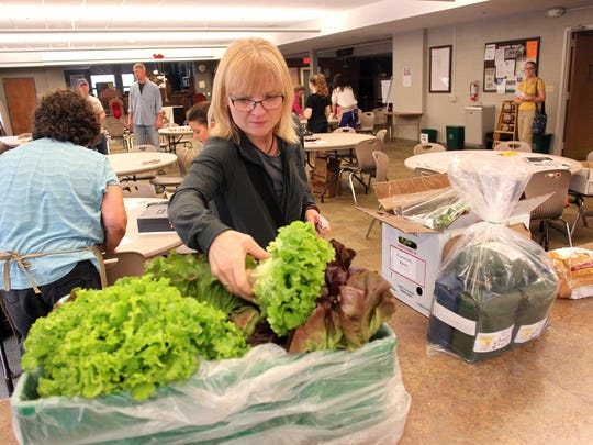 Kris Cameron of Coralville purchases fresh lettuce after picking up previously-ordered produce at the Iowa Valley Food Co-op's open house at Zion Lutheran Church on Wednesday, June 3, 2015. David Scrivner / Iowa City Press-Citizen