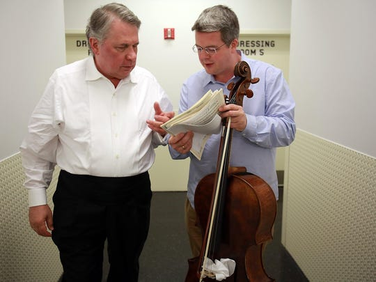 Cellist Paul Watkins, right, goes over his musical