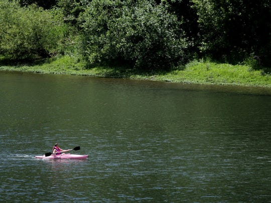 Above: A woman kayaks along the Willamette River in Salem on Thursday.