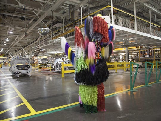 Artist Nick Cave wore one of his Soundsuits on the floor of Ford's Michigan Assembly Plant in Wayne on a visit in May.