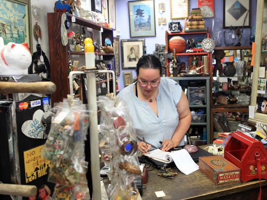 Margaret Roberts helps a customer at Artifacts on Friday. She was a longtime customer before she started working there five years ago.