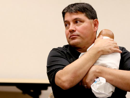 Instructor Larry Kramer demonstrates infant care with a doll during Boot Camp for New Dads on Monday, June 15, at Salem Hospital.