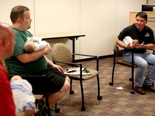 Instructor Larry Kramer, right, speaks to Matthew Langley, left, of Salem, and Greg Bakanoff, of McMinnville, during a demonstration with dolls Monday, June 15, at the Boot Camp for New Dads at Salem Hospital.