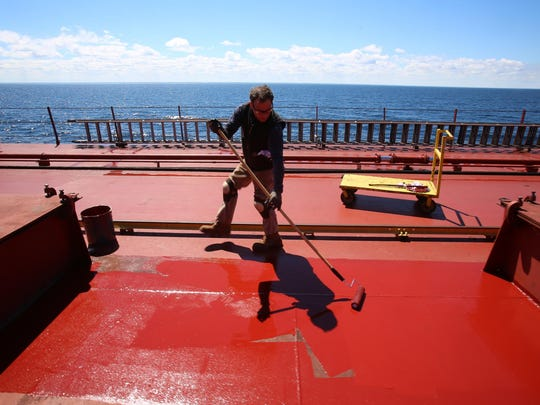 David Chance, a wheelsman, patches paint on the deck of the freighter Wednesday. Chance mixes the paint with sand to provide a nonskid surface because the deck often gets wet and slippery.