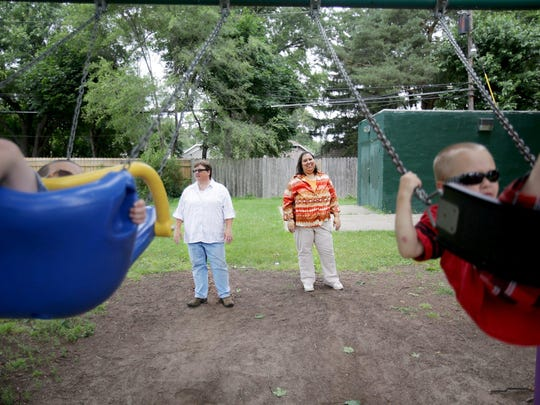 Dana Shaw, left, and Diane Shaw push their adopted sons on swings at a park in Ferndale on Friday. Dana and Diane Shaw were married during the few hours in March 2014 when same-sex marriages were legal in Michigan.