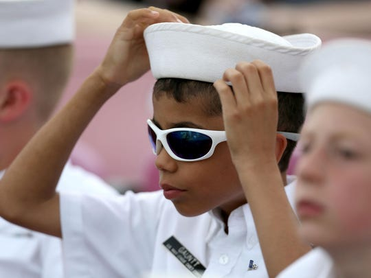 Matthew Gauntt, 11, with the U.S. Naval Sea Cadets of Salem adjusts his hat while watching the Volcanoes play the Tri-City Dust Devils on Saturday, July 4, 2015, in Keizer, Oregon.