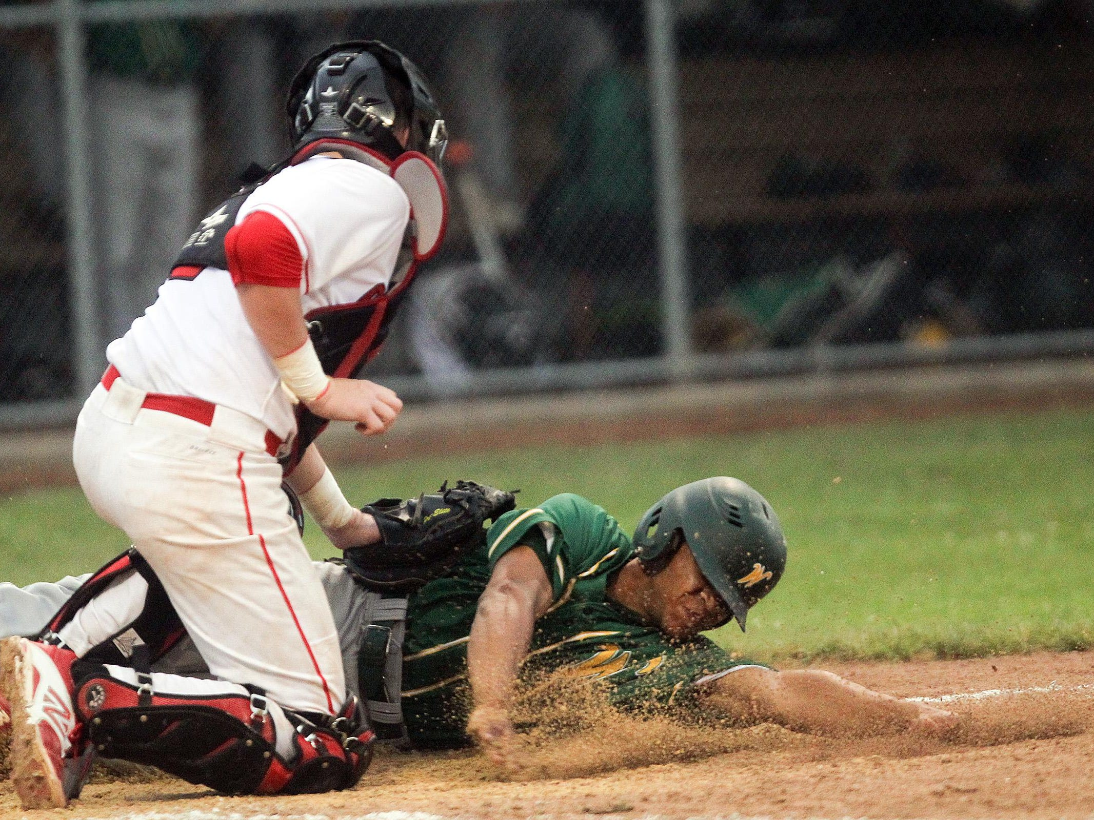 City High's Brett McCleary tags out West High's Mason Carter at home plate during their game at Mercer Park on Monday.