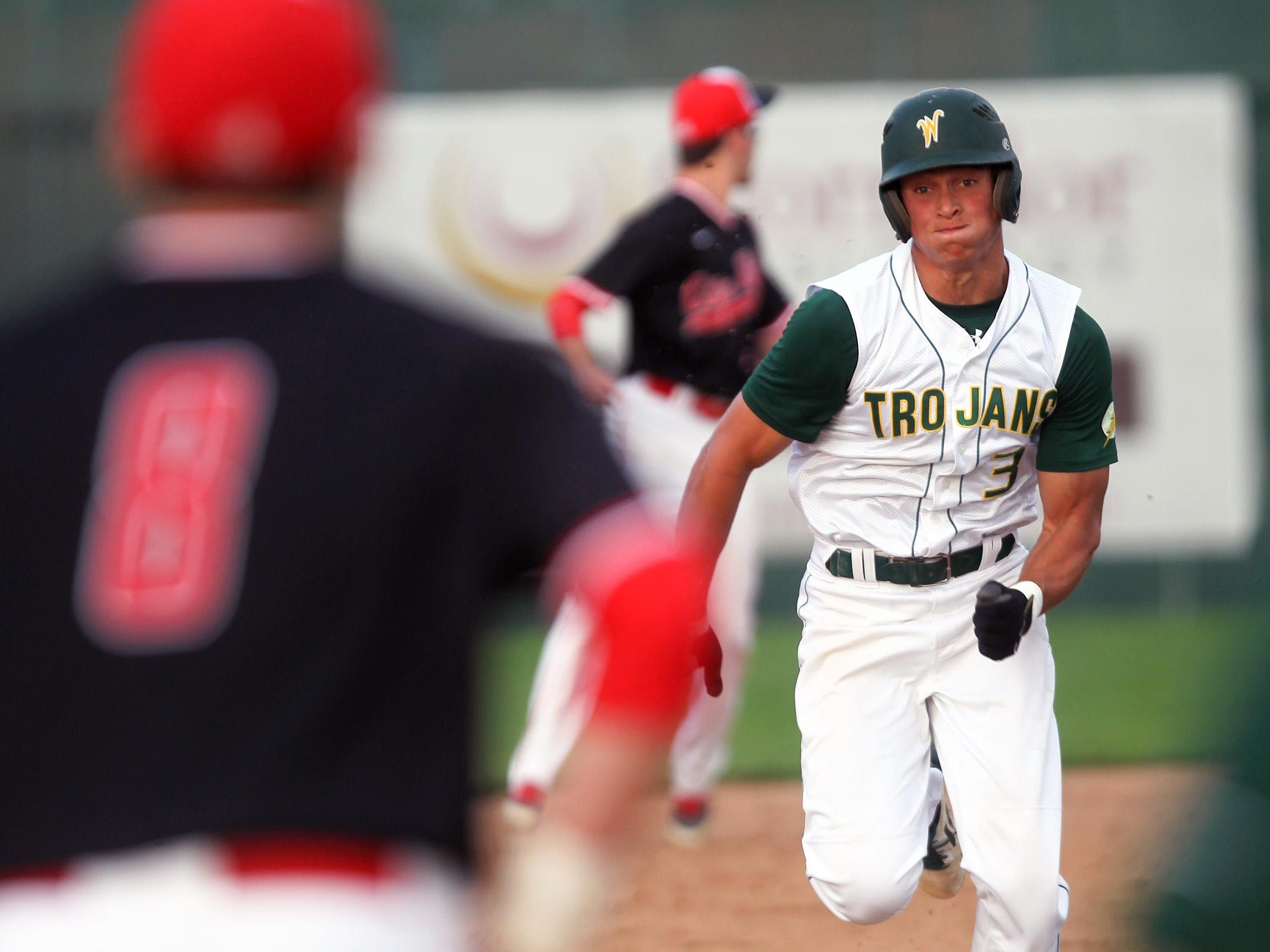 West High's Oliver Martin sprints to third base during the Trojans' home game against City High on Tuesday. West has won 11 out of 12 games after Tuesday's 2-1, walkoff vcitroy.