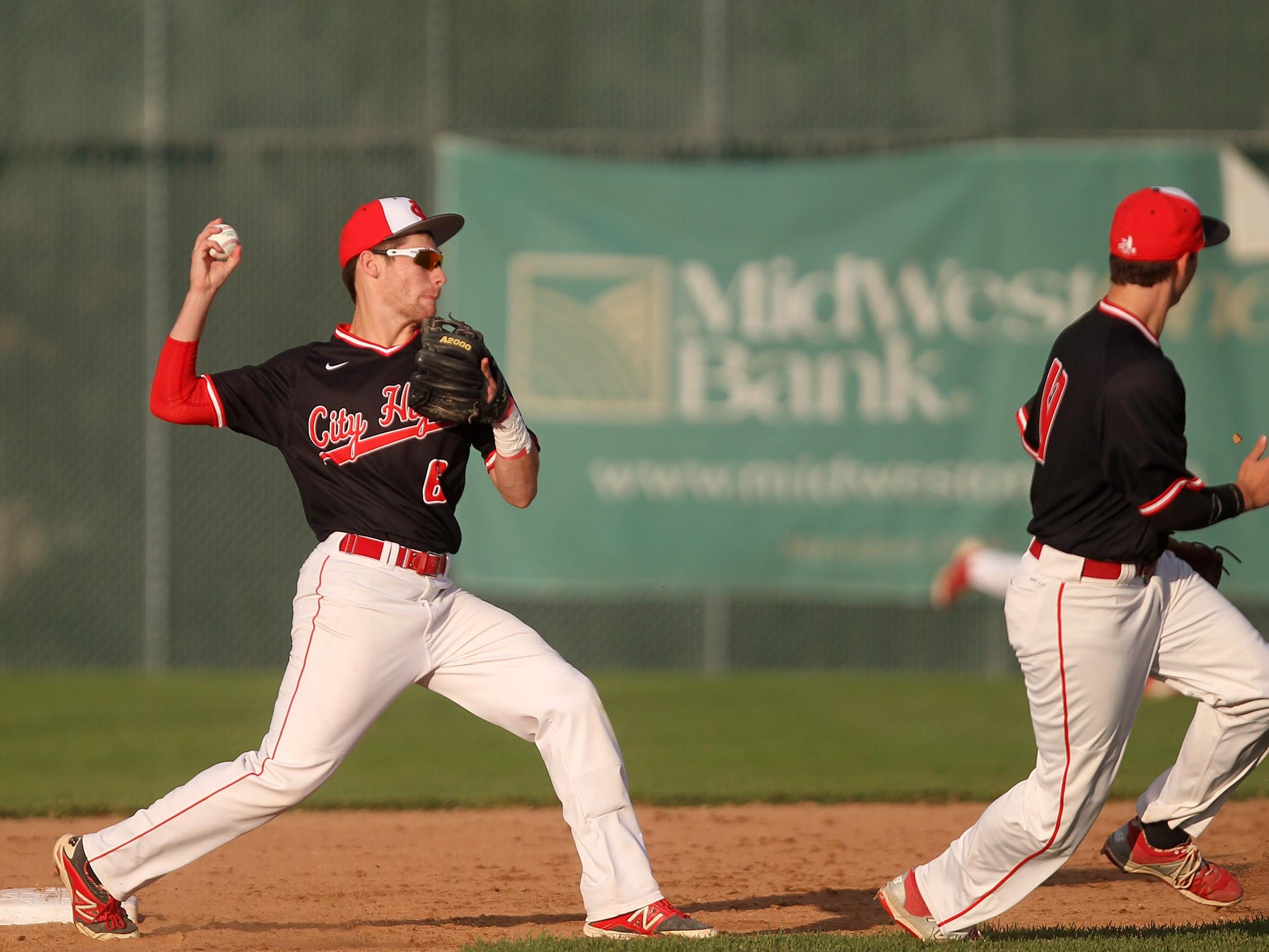 City High's Dylan Leigh throws to first base for a double play during the Little Hawks' game at West High on Tuesday, July 7, 2015. David Scrivner / Iowa City Press-Citizen