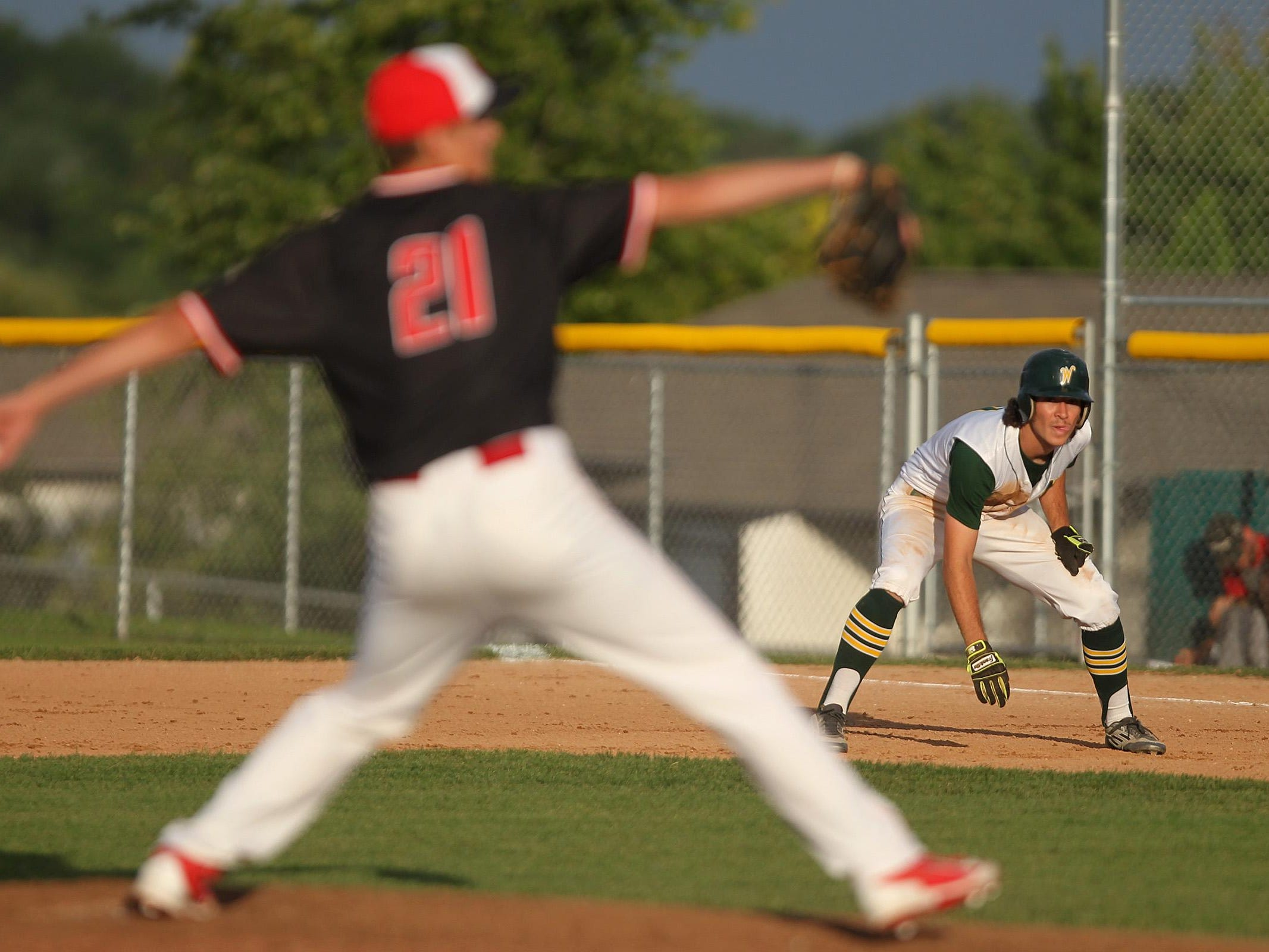 West High's Kevin DeLaney leads off first base as City High's Brady Cotton delivers a pitch on Tuesday.