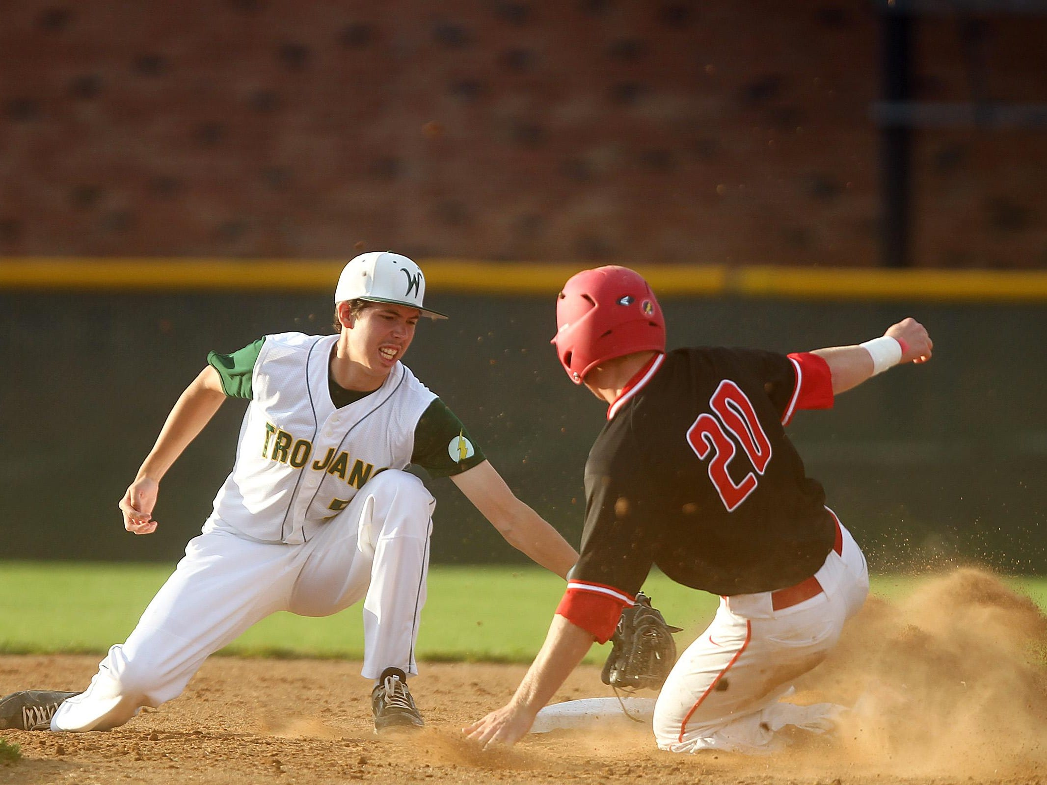 City High's Bryce Frantz safely slides past West High's Shane Sturtz during Tuesday's game. One night after grabbing an 8-7 victory in extra innings, West managed another one-run victory with a 2-1 triumph in the Trojans' last at-bat.