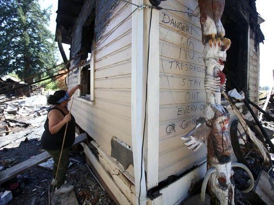 Debbie Wilson looks through debris at her home that burned on June 20. Photo taken on Wednesday, July 1, 2015, in Salem, Ore.