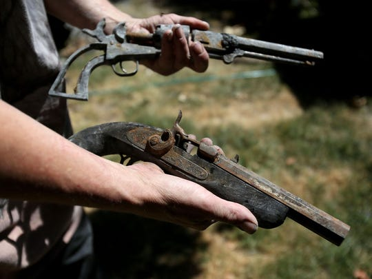 Randy Wilson holds a Colt .44, top, and a muzzleloader pistol that burned when his home was destroyed in a fire on June 20. Photo taken on Wednesday, July 1, 2015, in Salem, Ore.