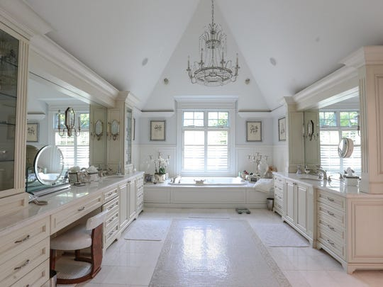 The master bathroom, with marble tile and mosaic inlay, also has a chandelier. The home was built in 1971 and remodeled in 2004. It's owned by an interior designer.