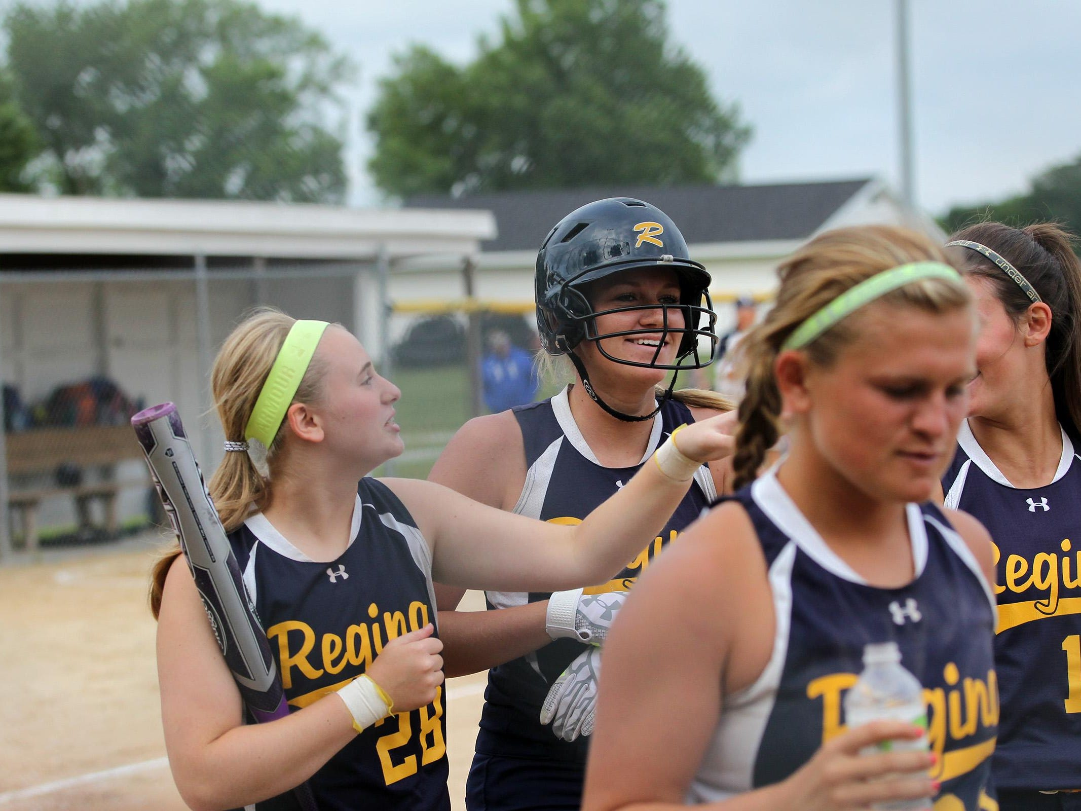 Regina's Kennedy Brown (center) heads to the dugout after her home run during the Regals' game against Columbus on Wednesday, July 8, 2015. David Scrivner / Iowa City Press-Citizen