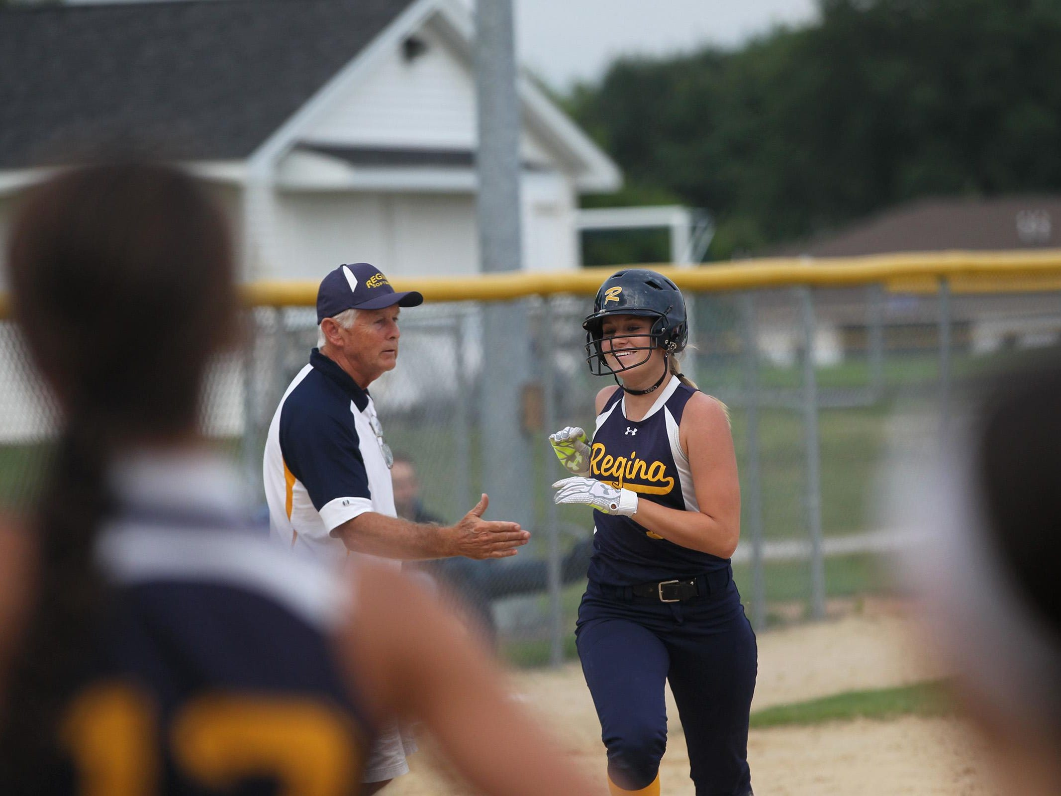 Regina's Kennedy Brown smiles as she runs in for a home run during the Regals' game against Columbus on Wednesday, July 8, 2015. David Scrivner / Iowa City Press-Citizen