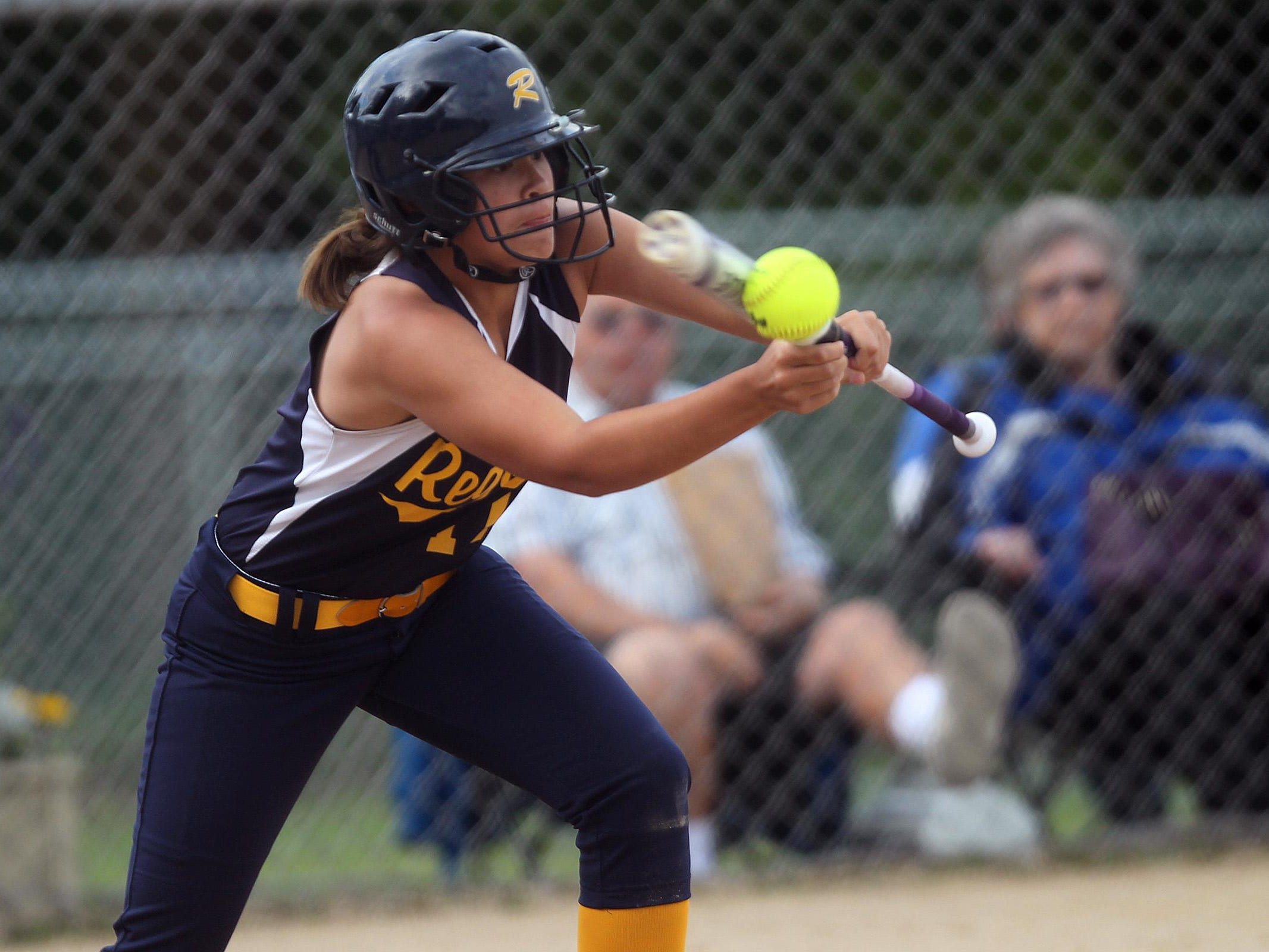 Regina's Emily Bonnett bunts the ball during the Regals' game against Columbus on Wednesday, July 8, 2015. David Scrivner / Iowa City Press-Citizen