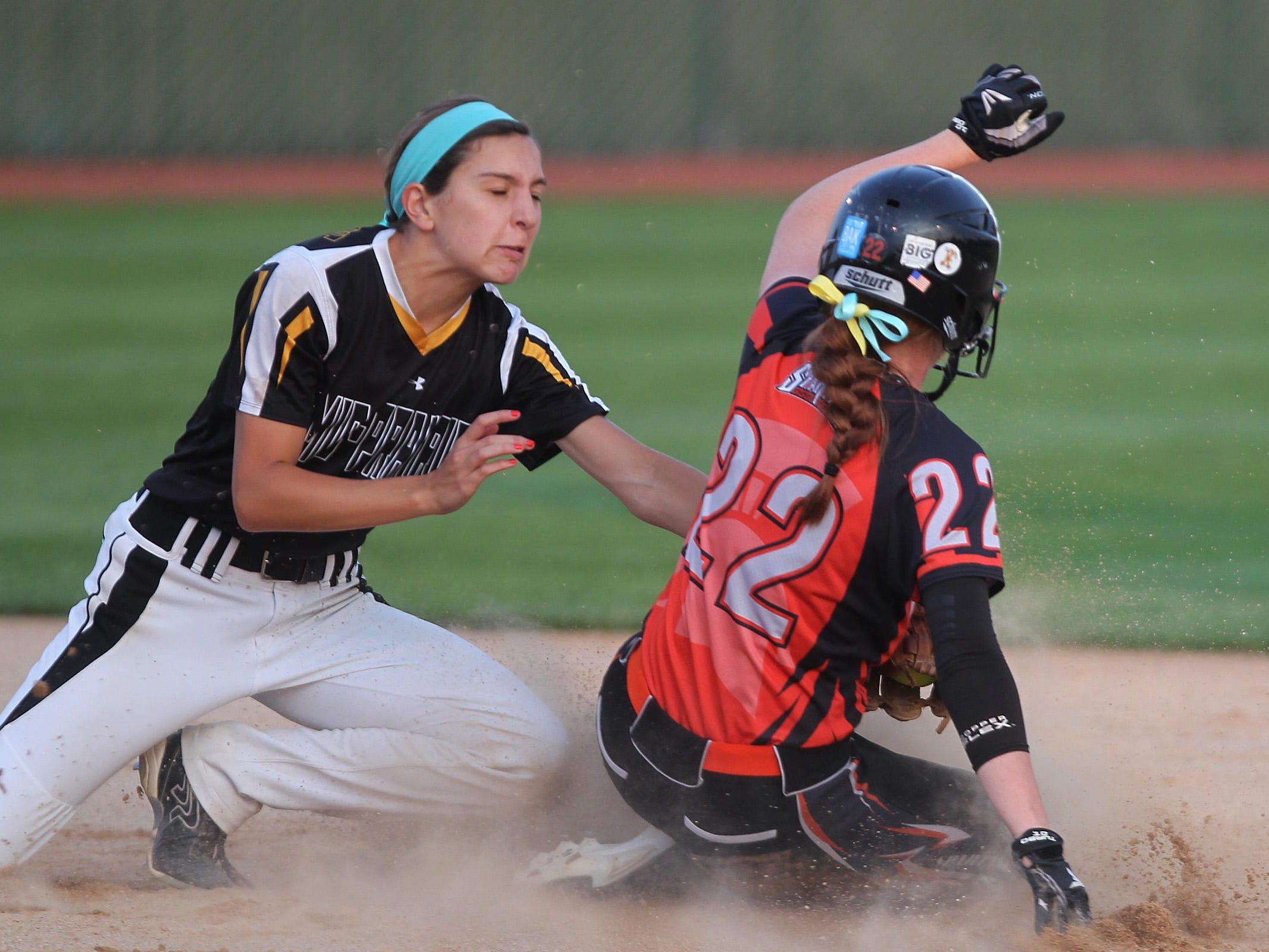 Solon's Jess Heick safely slides past Mid-Prairie's Alex Rath at second base during their regional game at Solon on Friday.