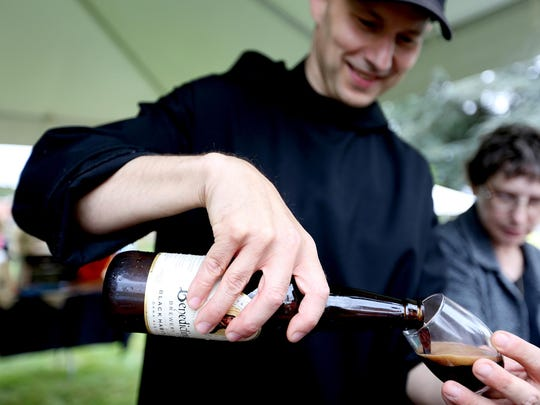 Father Martin Grassel pours a sample of beer brewed by the monks at the Mount Angel Abbey Saint Benedict Festival.