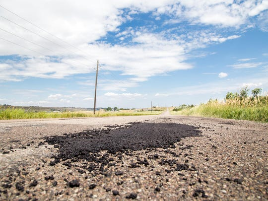 A recently filled pothole dries in the sun on Fox Farm Road, the site of Sunday morning's fatal car crash that took the life of 19-year-old Jennifer Elizabeth Boushee. A Montana Highway Patrol report said her vehicle first hit the pothole, skidded, lost a wheel and rolled.