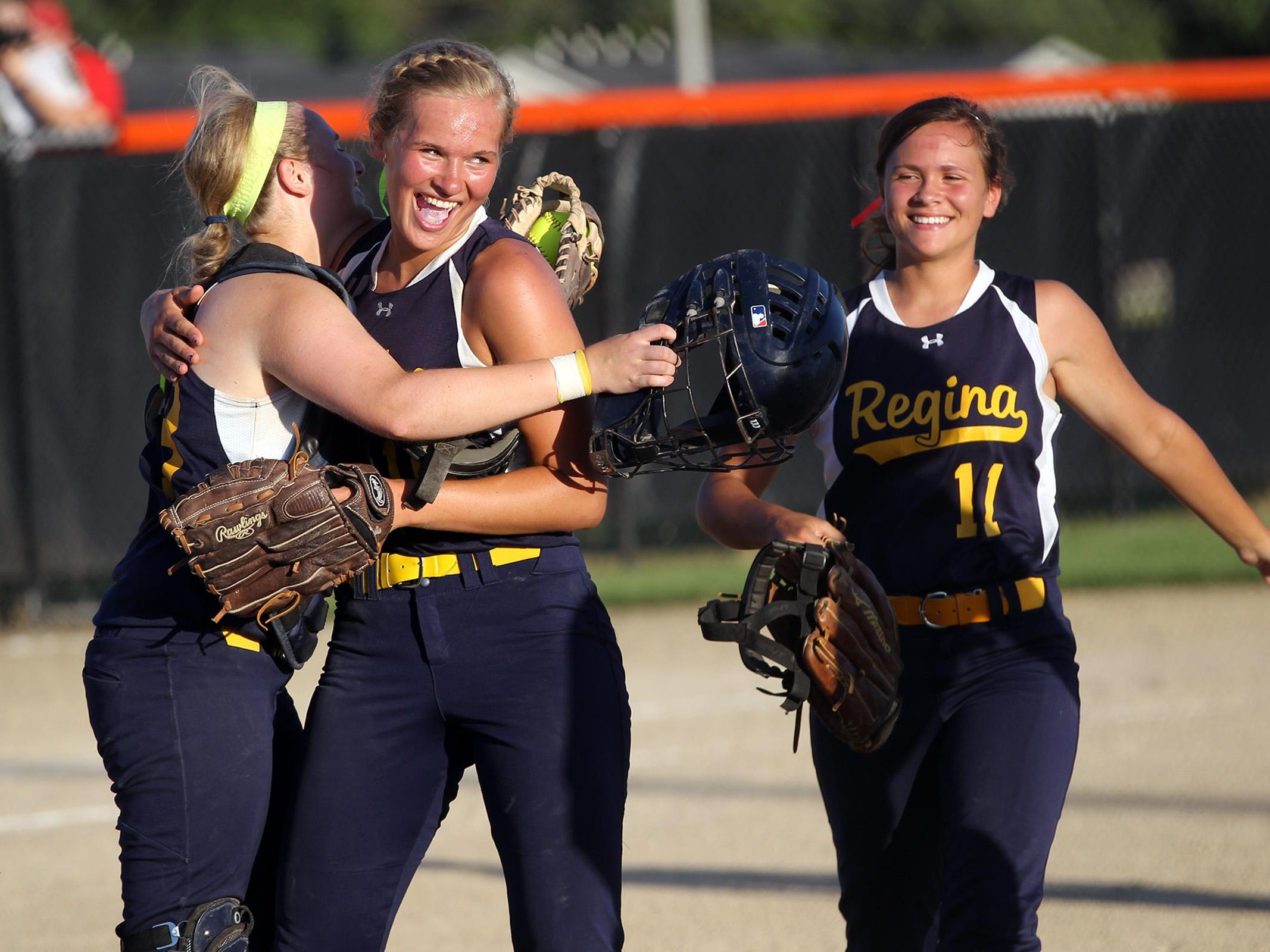 Regina pitcher Sarah Lehman, center, gets a hug from catcher Morgen Goedken following the Regals' Class 2A regional championship victory against Collins-Maxwell/Baxter in Grinnell on Monday. Regina won 5-1 to head to the state tournament.