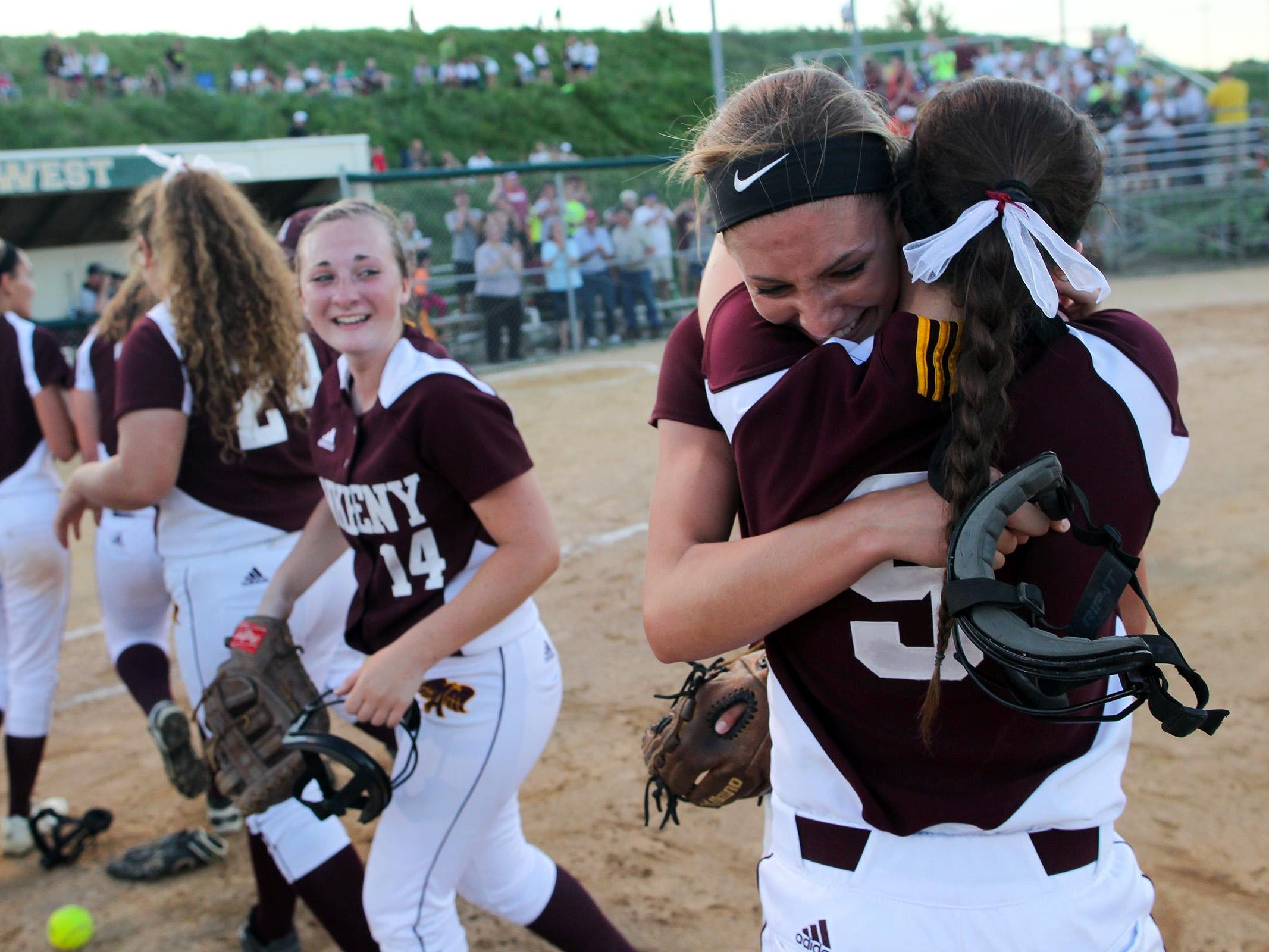 Ankeny pitcher Allison Doocy gets a hug from Olivia Brooks (9) following the Hawkettes' Class 5A regional championship game at West High on Tuesday, July 14, 2015. Ankeny won, 3-1, to head to state. David Scrivner / Iowa City Press-Citizen