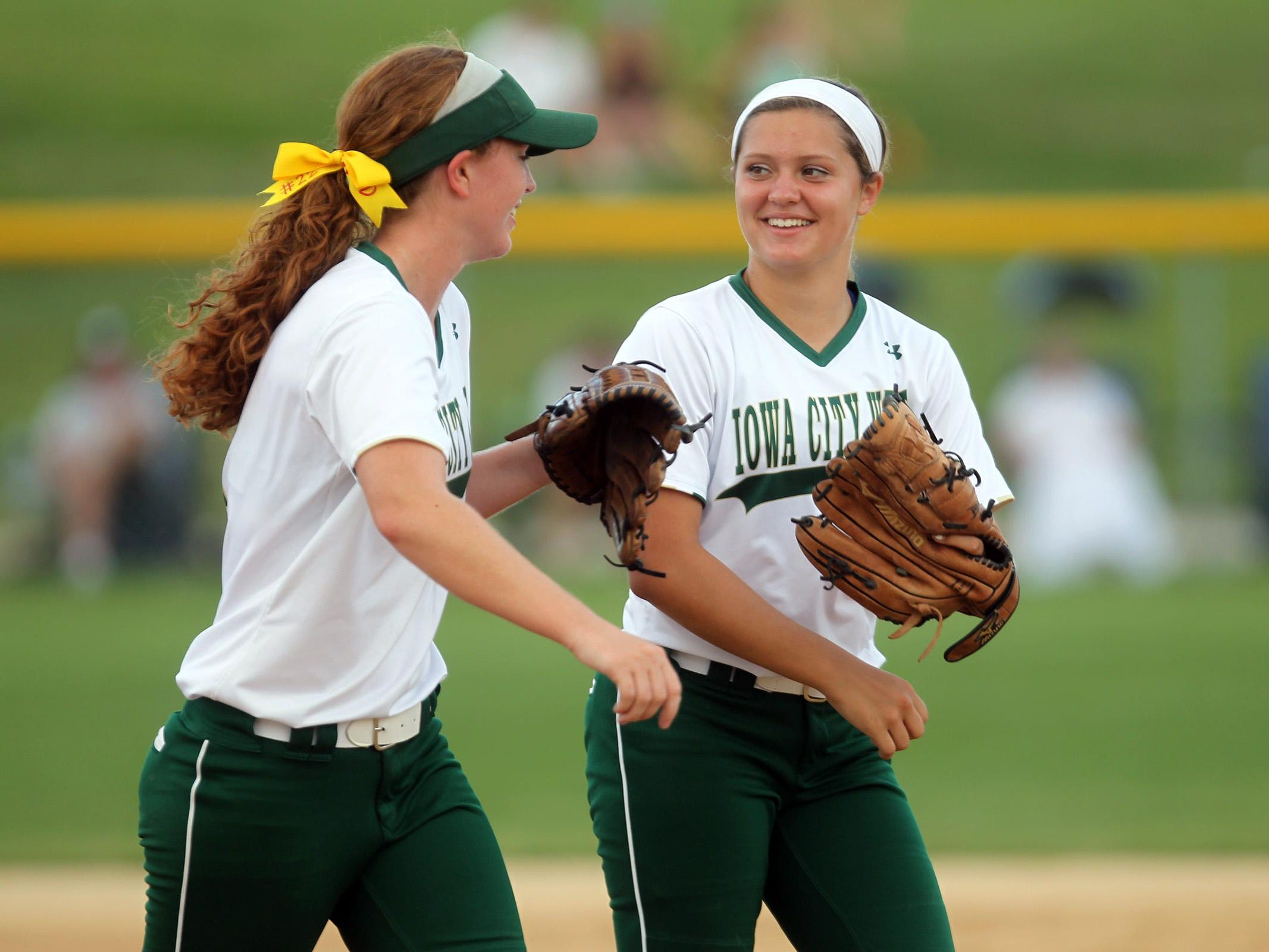 West High's Jessie Harder, left, high-five's Shea Lewis after a strikeout during their Class 5A regional championship game against Ankeny at West High on Tuesday, July 14, 2015. Ankeny won, 3-1, to head to state. David Scrivner / Iowa City Press-Citizen