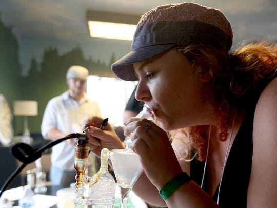 Lindsey Rinehart, 32, of Happy Valley, smokes hash oil as a judge July 10 during the 710 Festival at the PGN Lodge in Keizer.