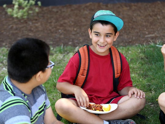 Gabriel Alvarez, right, jokes with friends during lunch at the Boys and Girls Club on Tuesday, July 14, 2015, in Salem. There's no free school lunches during the summer, so the USDA's Summer Food Service Program tries to close that gap by reimbursing meals offered to all kids throughout the summer. Locally the Boys and Girls Club is one of the organizations that partners with the USDA.