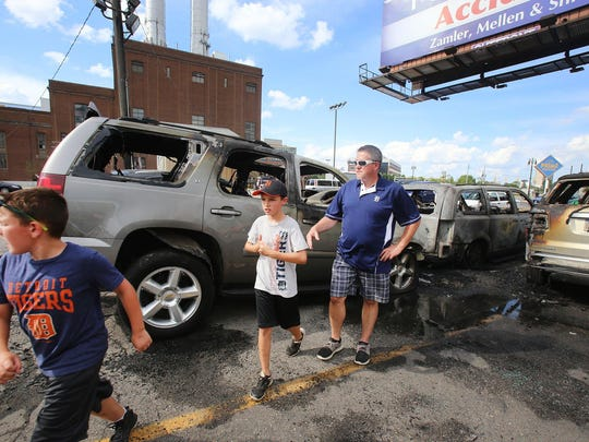 The Noonan family: Cole, 9, left, Parker, 10, center and their dad, Mike, all of Flushing, are reacting to their car being burned in a parking lot at Beaubien and Gratiot in downtown Detroit while they attended a Tigers baseball game Sunday, July 19, 2015. No one is hurt and the reason for the fire is unknown at this time.
