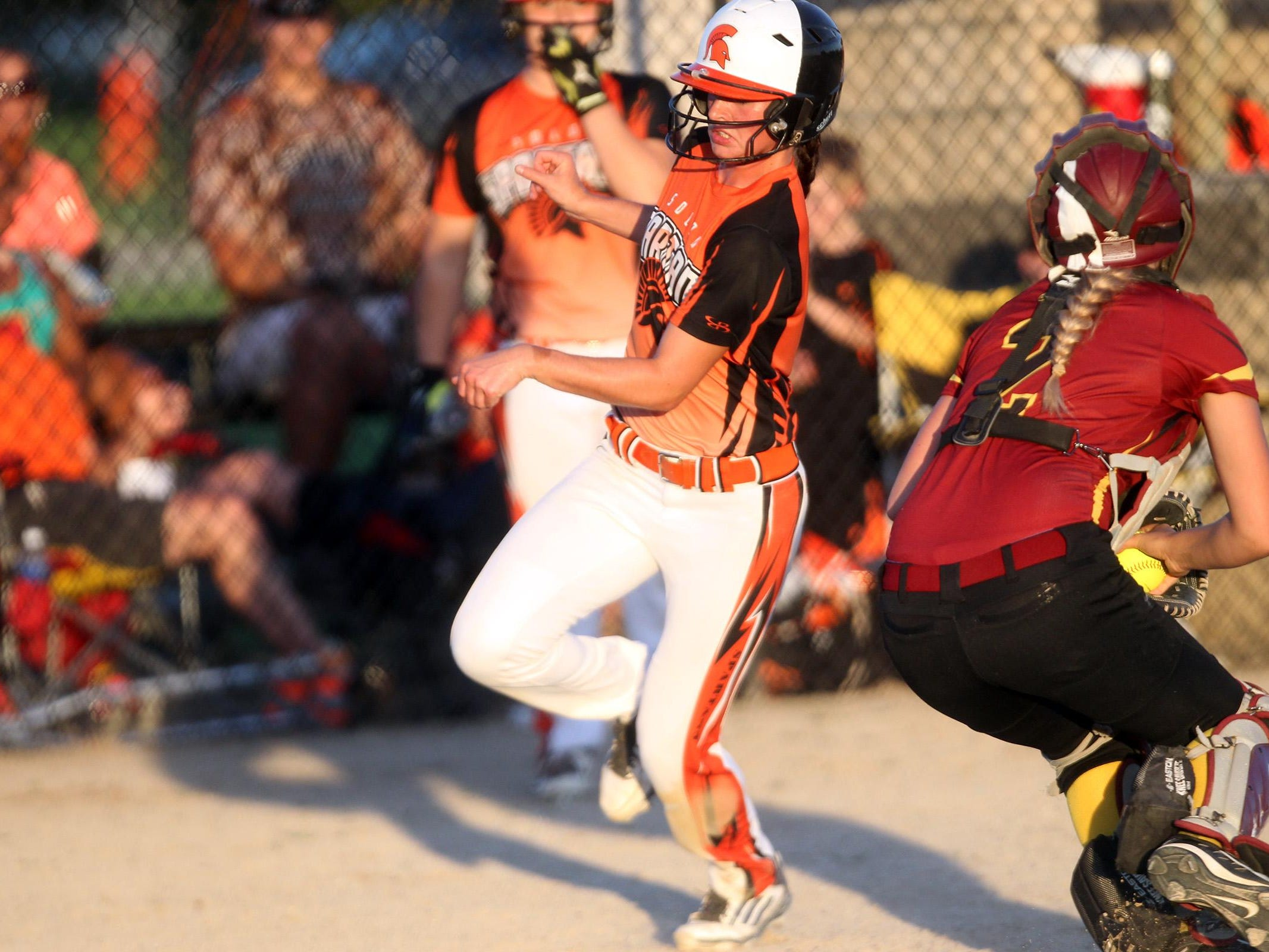 Solon's Sydney Lawson dodges PCM, Monroe's Courtney Bridges to run home during their Class 3A regional championship in Grinnell on Monday, July 13, 2015. David Scrivner / Iowa City Press-Citizen