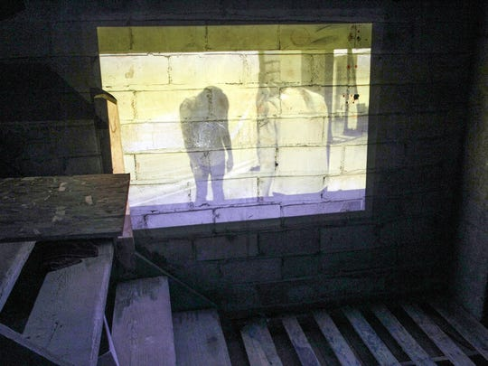 """A video is projected onto a wall in the basement of the Englert Theatre on Tuesday, July 21, 2015 in preparation for """"Ghost Story"""". The interactive play will allow audience members to tour areas of the Englert and immerse themselves into the story."""