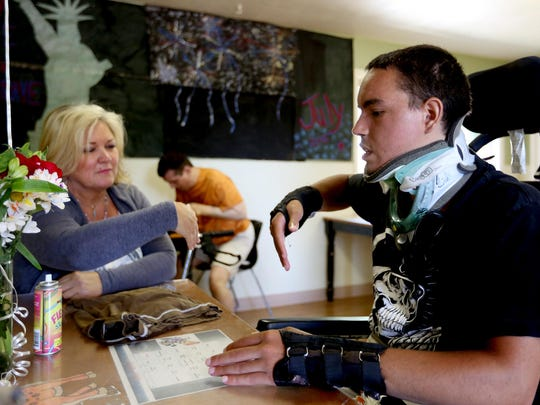 "Lyle Romans, 22, cannot fist bump because of his symptoms with terminal dermatomyositis and several other diseases, so he ""limp-fishes"" with Tami McNabb, the program manager, at the LEAP Ward center in northeast Salem on Friday, July 24, 2015."
