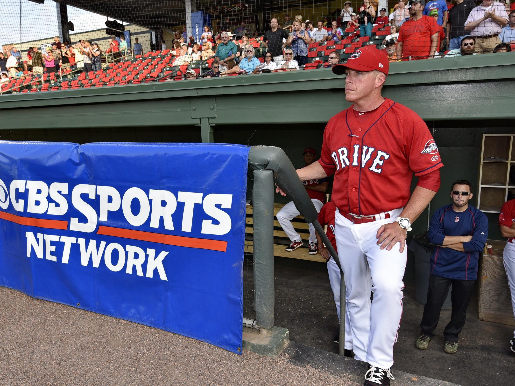 The CBS Sports Network displayed its banner in front of the Greenville Drive dugout as manager Darren Fenster waits for the game to begin Thursday.