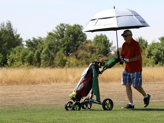 Don Penrose walks along a dry fairway Saturday, Aug. 1, 2015, at Oak Knoll Golf Course in Independence. The course focuses most of its water resources on putting greens and tees.