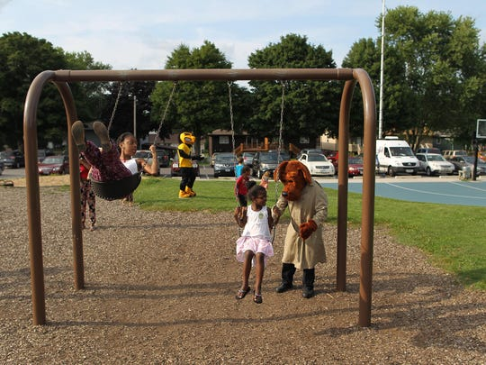 Children get a push from McGruff the Crime Dog at Wetherby Park during National Night Out on Tuesday, Aug. 4, 2015.