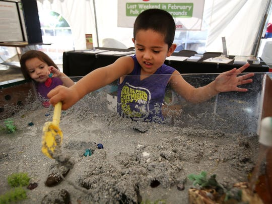 Evan Camara, 4, redirects water in a stream table as his sister, Gabryelle, 2, looks on at the Polk County Annual Fair on Friday, Aug. 7, 2015, in Rickreall, Ore.