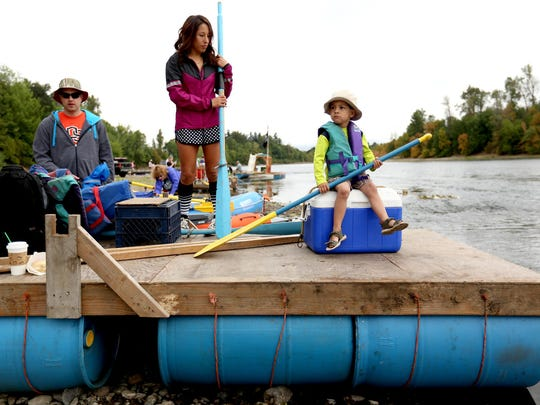 Dylan Bermudez, 3, of Independence, sits with his aunt Ashley Bermudez, 25, of Independence, and Brian Simila, 31, of Portland, on their homemade raft Saturday at Riverview Park in Independence before the Great Willamette River Raft Race.