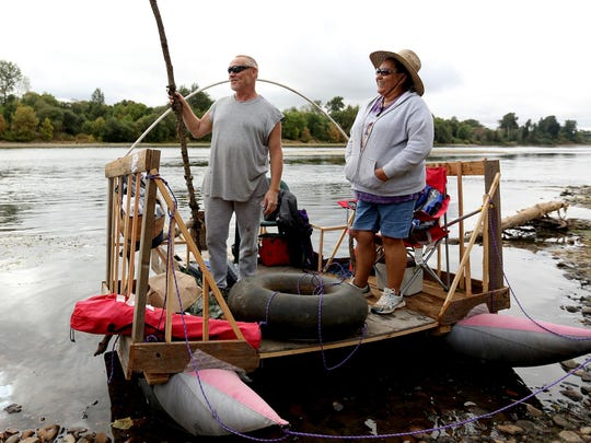 Ken Wynne, 53, and Susie Savant, 50, both of Independence, wait on their homemade raft Saturday before the Great Willamette River Raft Race at Riverview Park in Independence.